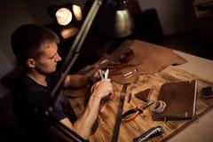 Arbeitsprozeß des Ledergürtels in der ledernen Werkstatt Mann, der das In Handarbeit machen des Werkzeugs und das Arbeiten hält G stockfotos