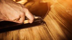 Arbeitsprozeß des Ledergürtels in der ledernen Werkstatt Mannholdingwerkzeug Gerber in der alten Gerberei Hölzerne Tabelle Lizenzfreies Stockfoto