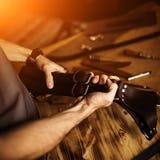 Arbeitsprozeß des ledernen Handwerks in der Werkstatt Bemannen Sie das Halten Fotograf ` s von Gurt für Kamera Hölzerner Hintergr Stockfotografie