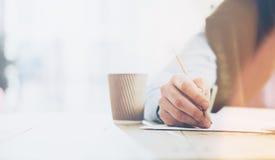 Arbeitsprozeß Geschäftsmann, der am hölzernen Tisch mit neuem Projekt arbeitet Halten der Bleistifthand, der Zeichen Dokument und Lizenzfreies Stockbild