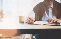 Arbeitsprozeß Kundenbetreuer, der am hölzernen Tisch mit neuem Geschäftsprojekt arbeitet Halten der Bleistifthand, Zeichendokumen Stockfotografie