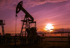 Arbeitspumpensteckfassung im Ölfeld Sonnenuntergang Stockfotografie