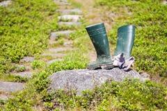 Arbeitsregen-Stiefel und Handschuhe auf Felsen Stockfoto