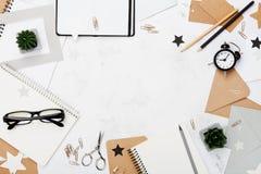 Arbeitsschreibtisch mit Bürozubehör, Brillen, Wecker und säubern Draufsicht des Notizbuches Flache Lage Kopieren Sie Raum für Tex Lizenzfreie Stockbilder