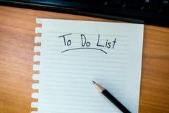 Arbeitsschreibtisch mit dem Schreiben, zum der Liste zu tun Stockbild