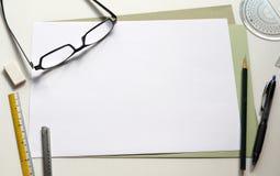 Arbeitsschreibtisch mit leerem Papier Lizenzfreie Stockbilder