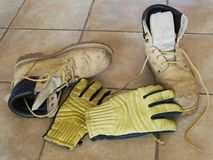 Arbeitsschuhe und Handschuhe Stockfotografie