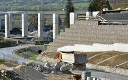 Arbeitsstandort mit den Säulen, nachhaltiger Wand und den LKWs, die auf die Straße fahren Stockbild