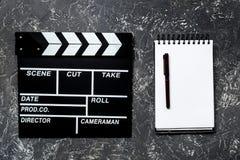 Arbeitstabelle des Produzenten Filmclapperboard und -notizbuch auf Draufsicht des grauen Steinhintergrundes Lizenzfreies Stockfoto