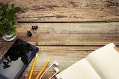 Arbeitstabelle mit ipad Schirm, offenes Notizbuch-ANG-Grün verlässt Kopieren Sie Platz Rustikaler hölzerner Hintergrund Beschneid lizenzfreies stockbild
