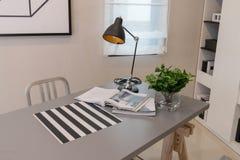 Arbeitstabelle mit Lampe und Buch Stockbilder
