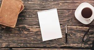 Arbeitstabelle mit Notizblock, Stift, Schauspielen, Kaffee und Büchern Lizenzfreies Stockbild