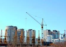 Arbeitsturmkran auf dem Hintergrund von Wohnhäusern Lizenzfreies Stockfoto