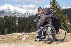 Arbeitsunf?higer Mann auf Rollstuhl unter Verwendung der Kamera in der Natur, sch?ne Berge fotografierend lizenzfreie stockfotografie