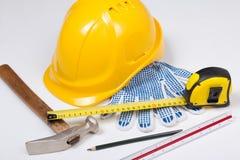 Arbeitswerkzeuge des Erbauers und gelber Sturzhelm über Weiß Lizenzfreies Stockbild