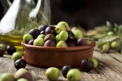 Arbequina olives from Catalonia, Spain. An earthenware bowl full of arbequina olives from Catalonia, Spain, a cruet with olive oil and some twigs of olive tree Royalty Free Stock Photos