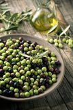 Arbequina olives from Spain. Closeup of an earthenware bowl full of arbequina olives from Catalonia, Spain, a cruet with olive oil and some twigs of olive tree Royalty Free Stock Image