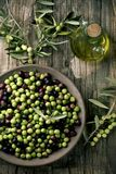 Arbequina olives from Spain. High-angle shot of an earthenware bowl full of arbequina olives from Catalonia, Spain, a cruet with olive oil and some twigs of Stock Photo
