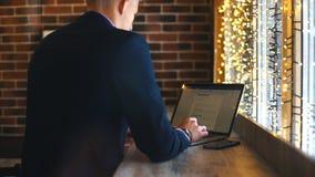 Arbeta från kafét Gladlynt ung man i smarta tillfälliga kläder som ser bärbara datorn och sitter nära fönster i idérikt kontor stock video