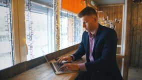 Arbeta från kafét Gladlynt ung man i smarta tillfälliga kläder som ser bärbara datorn och sitter nära fönster i idérikt kontor arkivfilmer
