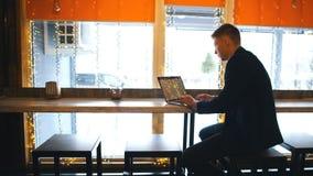 Arbeta från kafét Gladlynt ung man i smarta tillfälliga kläder som ser bärbara datorn och sitter nära fönster i idérikt kontor lager videofilmer