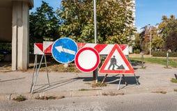 Arbeta framåt det varnande tecknet för konstruktionsplatsen med vägbarrikader och trafikvarningsbarriärer på gatan royaltyfri bild