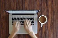 Arbeta hemifrån på bärbara datorn med morgonkaffe Fotografering för Bildbyråer