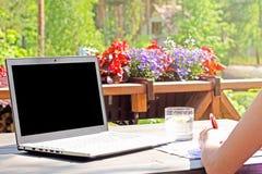 Arbeta hemifrån, tabellen med bärbara datorn på terrass Royaltyfri Foto