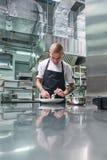 Arbeta i en restaurang Vertikal stående av den yrkesmässiga manliga kocken med tatueringar på hans armar som garnerar hans maträt royaltyfria bilder