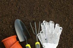 Arbeta i trädgården hjälpmedel, handskar och blomkrukor på jordningen i garen fotografering för bildbyråer