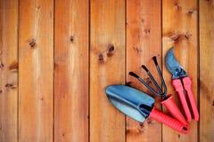 Arbeta i trädgården hjälpmedel och objekt på gammal träbakgrund Arkivfoto
