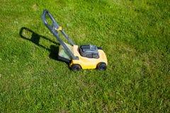 Arbeta i trädgården Meja gräsmatta med den gula gräsklipparen Royaltyfria Foton
