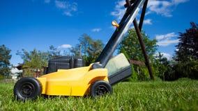Arbeta i trädgården Meja gräsmatta med den gula gräsklipparen Royaltyfri Bild