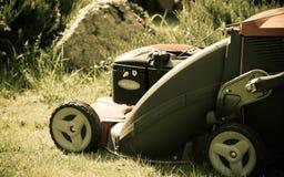 Arbeta i trädgården Meja grön gräsmatta med den röda gräsklipparen Arkivbilder
