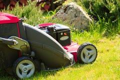 Arbeta i trädgården Meja grön gräsmatta med den röda gräsklipparen Royaltyfria Foton
