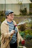 Arbeta i trädgården och folkbegrepp - lycklig hög kvinna som bevattnar gräsmatta vid den trädgårds- slangen på sommar arkivfoton