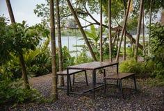 Arbeta i trädgården tabellen med stol nära en flod och trädet för att koppla av Royaltyfri Foto