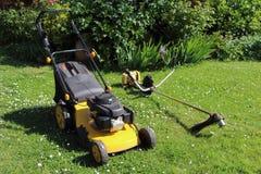 Arbeta i trädgården utrustning, gräsklippningsmaskinen och borsteskäraren Royaltyfri Foto