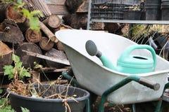 Arbeta i trädgården utrustning: vagnen som bevattnar kan, spjällådor, gödningsmedel och blommor royaltyfri fotografi