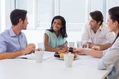 Arbeta kollegor som pratar i bräderum, medan tycka om kaffe och muffin Royaltyfria Foton