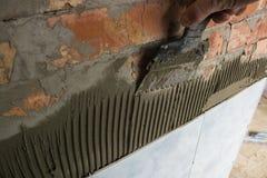 Arbeta med mortel som belägger med tegel en badrumvägg fotografering för bildbyråer