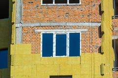 Arbeta på de yttre väggarna av glasullisolering och murbruk Arkivbild