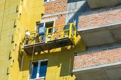 Arbeta på de yttre väggarna av glasullisolering och murbruk Arkivfoto