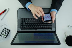 Arbeta på en bärbar dator och använda smartphonen från över Arkivfoton