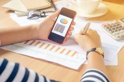Arbeta på ett skrivbord som är numeriskt på mobil analys, finansiell redovisning Graphing internet, Arkivfoton