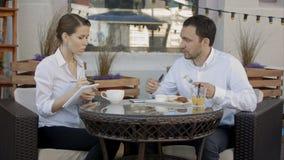 Arbeta på projekt tillsammans Affärspartners som har en konversation på ett kafé arkivfilmer