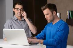 Arbeta på projekt. Två gladlynta affärsmän som står near lapto arkivfoton
