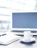 Arbeta skrivbordet med en kopp kaffedatorbärbar dator, anteckningsboken, penna Royaltyfri Foto
