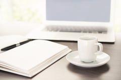 Arbeta skrivbordet med en kopp kaffedatorbärbar dator, anteckningsboken, penna Arkivfoto