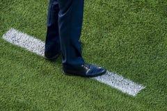 Arbeta som privatlärare åt anseendet bredvid kritalinje på fotbollfält fotografering för bildbyråer